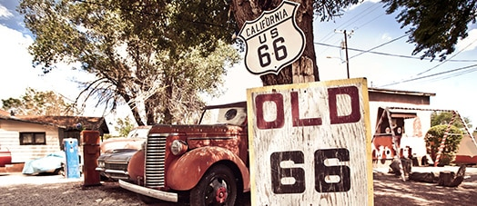 Route 66 sign by old red truck