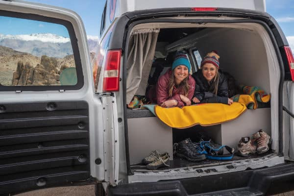2 girls laying in back of campervan