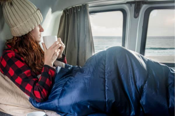 female in sleeping bag with coffee
