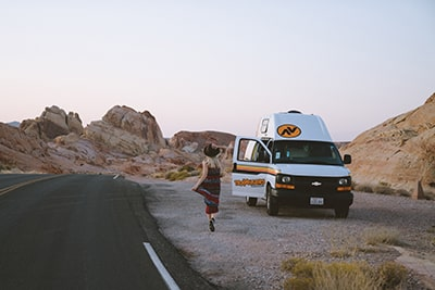 female running toward campervan in Valley of Fire