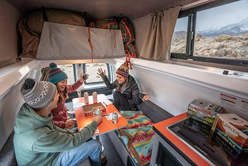 group of friends in a campervan with games