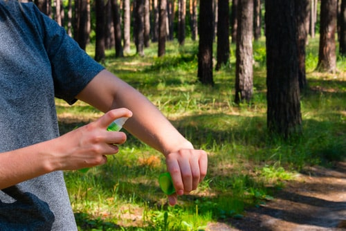 Person spraying insect repellent