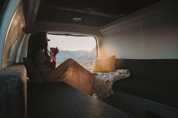 Female sitting in the back of a campervan