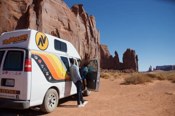 Man standing next to campervan enjoying view