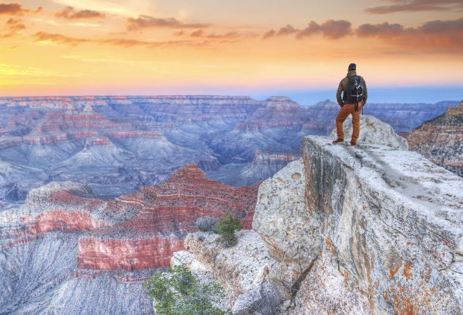 Hiker standing on edge of Grand Canyon