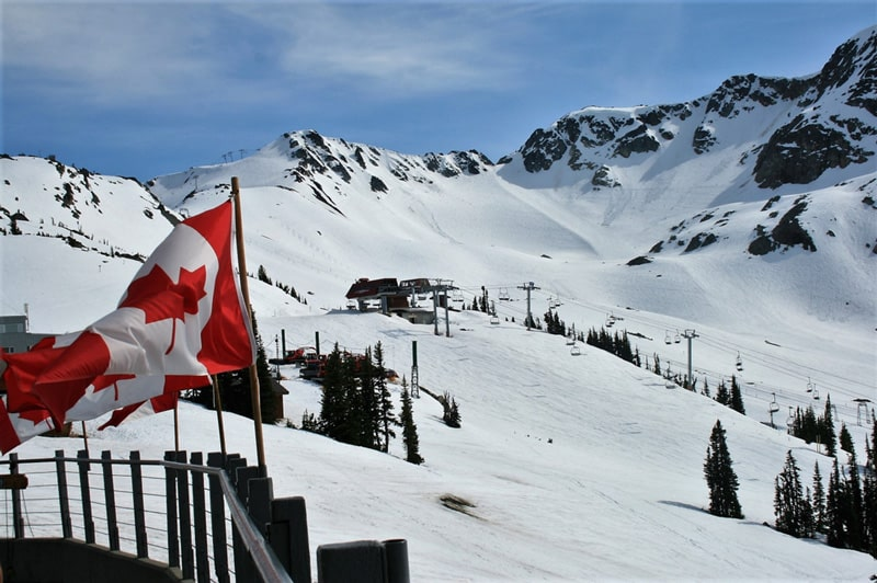 Snowy mountains and Canadian flag at Whistler Blackcomb, Canada